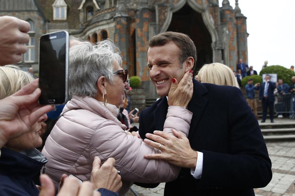 الرئيس الفرنسي إيمانويل ماكرون يبتسم لأحد مؤيديه بعد التصويت في الانتخابات البرلمانية الأوروبية في لو توكيه، شمال فرنسا، الأحد 26 مايو/ أيار 2019