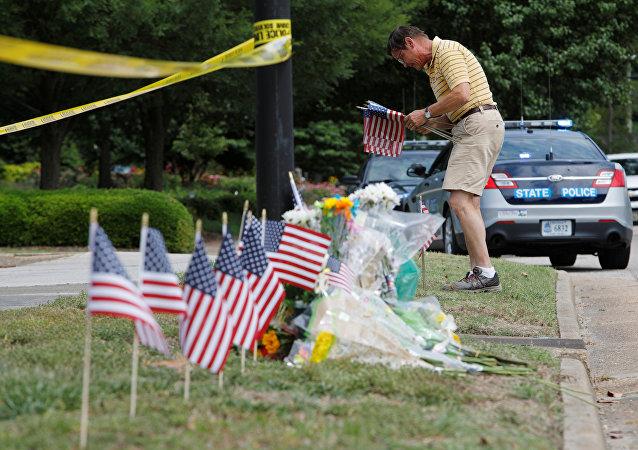 أحد السكان المحليين يضع أعلاما في نصب تذكاري مؤقت خارج مبنى حكومي في البلدية وقع فيه حادث إطلاق نار في فيرجينيا بيتش، فرجينيا، الولايات المتحدة، 1 يونيو/حزيران 2019