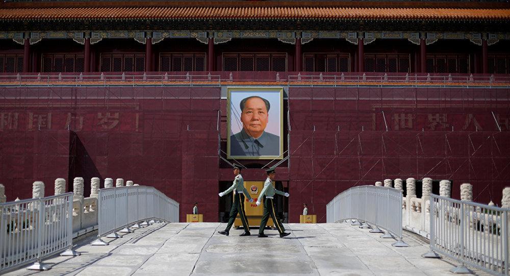 ضباط أمام صورة الزعيم الصيني الراحل ماو تسي تونغ في ميدان تيانانمين في العاصمة الصينية بكين
