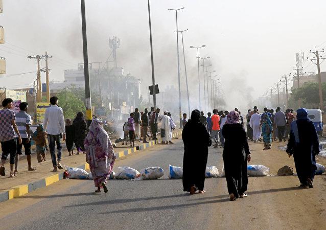 متظاهرون سودانيون يتجمعون عند حاجز في أحد الشوارع مطالبين المجلس العسكري الانتقالي في البلاد بتسليم السلطة إلى المدنيين