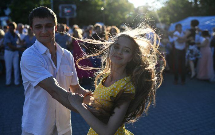 شخصان يافعان يرقصان على أنغام حفل موسيقي في ساحة ناخيموف في سيفاستوبول، القرم، روسيا