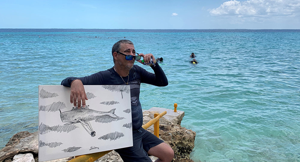 الفنان الكوبي ساندور غونزاليس يتحدث إلى وسائل الإعلام بعد رسمه تحت الماء في بونتا بيرديز