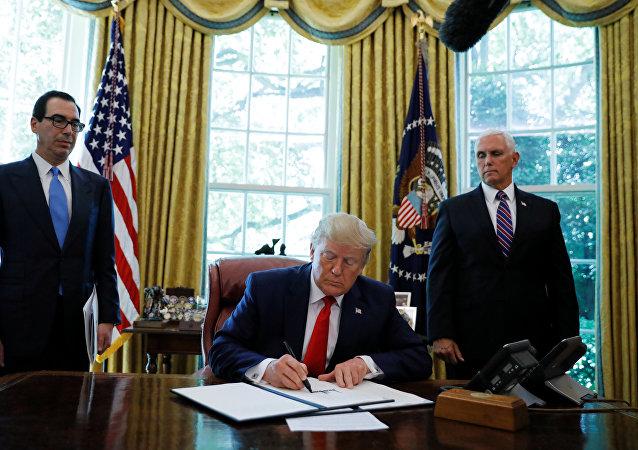 الرئيس الأمريكي دونالد ترامب يوقع على أمر تنفيذي يفرض عقوبات جديدة على إيران بينما ينظر وزير الخزانة ستيفن منوشين ونائب الرئيس مايك بينس في المكتب البيضاوي للبيت الأبيض في واشنطن