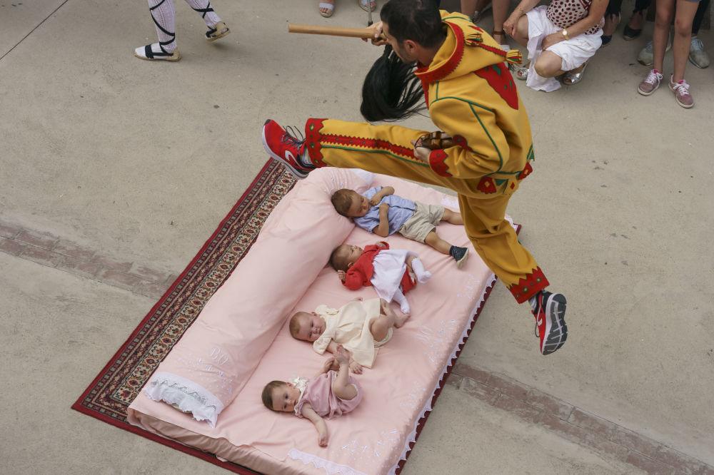 شخصية كولاتشوف تمثل الشيطان، تقفز فوق الأطفال في الشارع أثناء مهرجان إل كولاتشو في بلدة كاستيليو دي مورسيا، 23 يونيو/ حزيران 2019