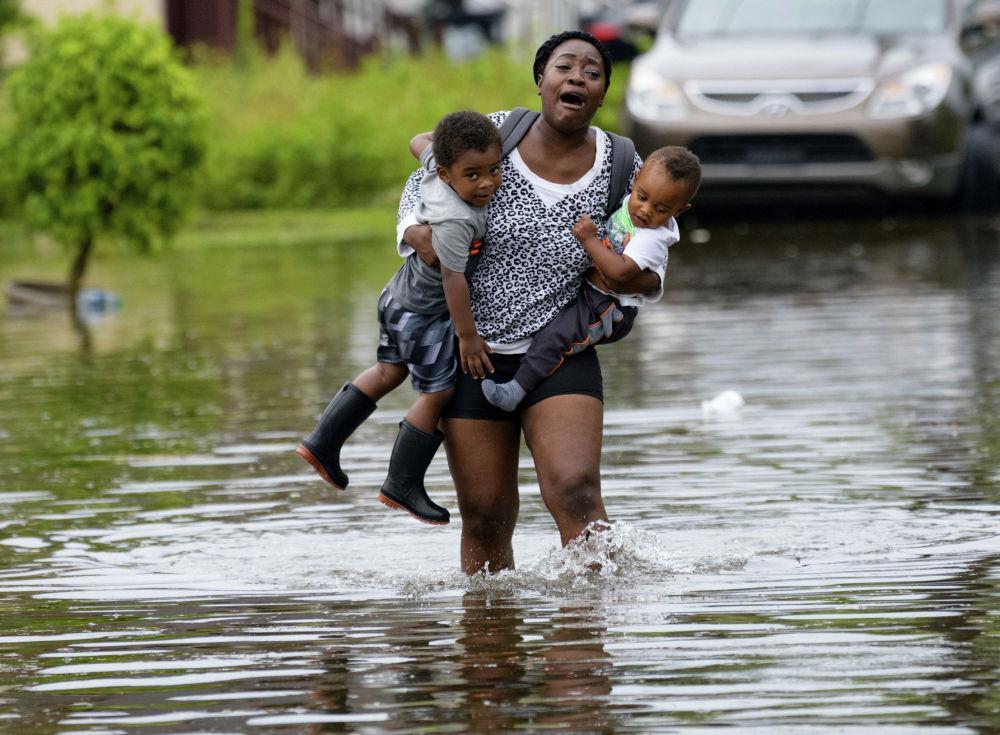 أم تحمل أطفالها بعد طوفان في نيو أورليانز، 10 يوليو/ تموز 2019