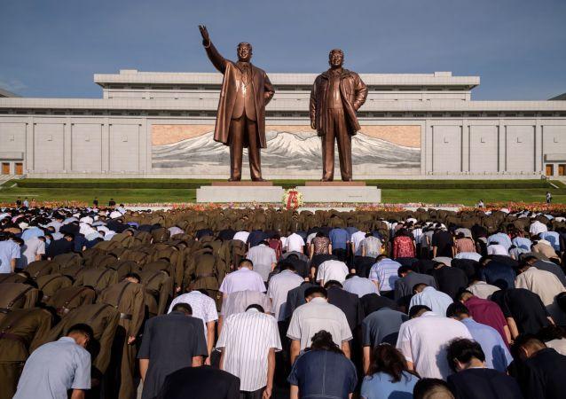 سكان بيونغ يانغ خلال دقيقة صمت أمام النصب التذكاري لكيم إيل سونغ وكيم جونغ إيل في يوم الذكرى الـ 25 لوفاة كيم إم سونغ، بيونغ يانغ، كوريا الشمالية 8 يوليو/ تموز 2019