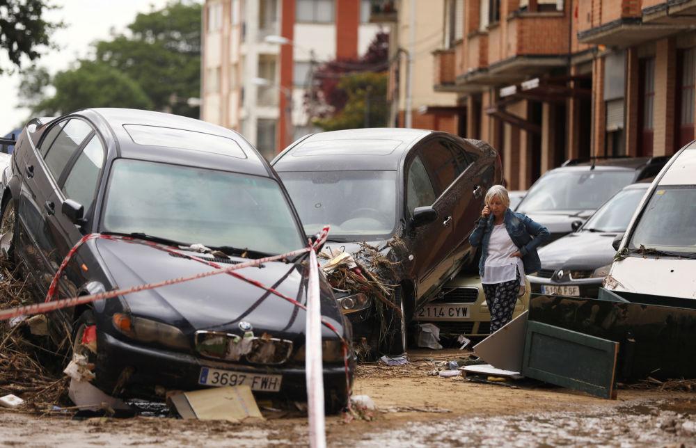 امرأة تتحدث على الهاتف بجوار السيارات المدمرة بعد هطول أمطار غزيرة في تافالا، إسبانيا ، 9 يوليو/ تموز 2019
