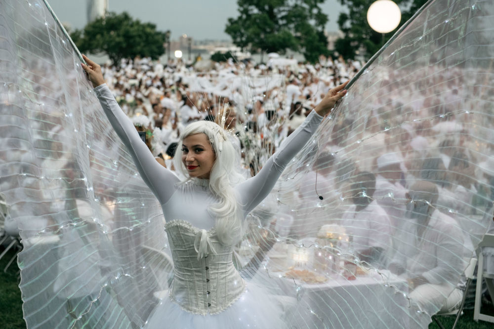 مشاركون في حفل عشاء دينر أون بلانك السنوي في حي مانهاتن في 17 يوليو/ تموز 2019 في مدينة نيويورك. حيث تجمع أكثر من 5500 ضيف لحفل منبثق سنويًا، والذي يلتزم بقواعد اللباس الصارمة البيضاء بالكامل. تعود فعالية دينر أو بلانك (Diner En Blanc) في الأصل إلى باريس عام 1988، وازدادت شعبيتها وتستضيفها مدن في مختلف أنحاء العالم.