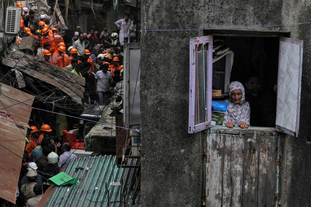 امرأة من السكان المحليين تنظر من النافذة بينما يبحث رجال الإنقاذ عن ناجين بعد انهيار مبنى في مومباي بالهند، 16 يوليو/ تموز 2019