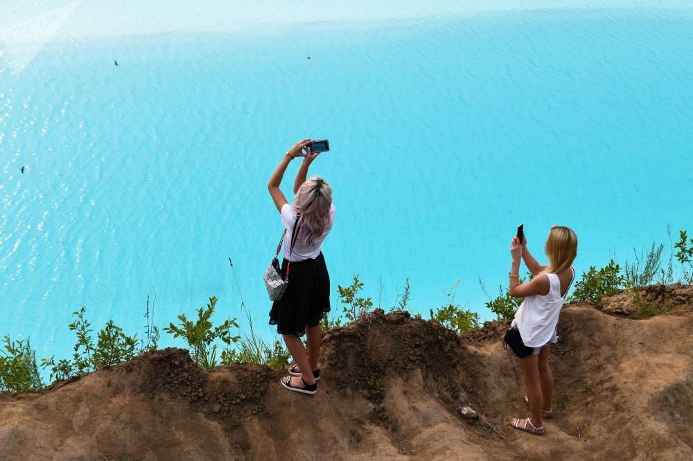 فتاة تلتقط صورة للبحيرة القرمزية، التي أطلق عليها أهالي المنطقة المحليون بـ جزر المالديف، قرب محطة الطاقة الحرارية في نوفوسيبيرسك، روسيا 11 يوليو/ تموز 2019