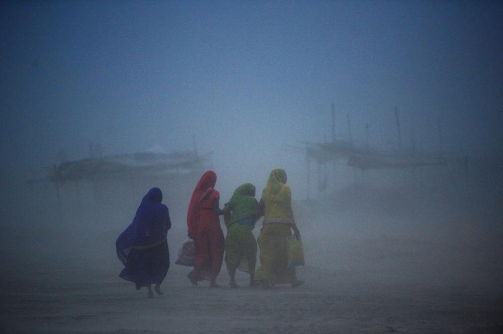 نساء هنديات يمشين أثناء عاصفة ترابية في سانجام، التقاء أنهار الغانج ويامونا وساراسواتي الأسطوري، في الله أباد في 16 يوليو/ تموز 2019