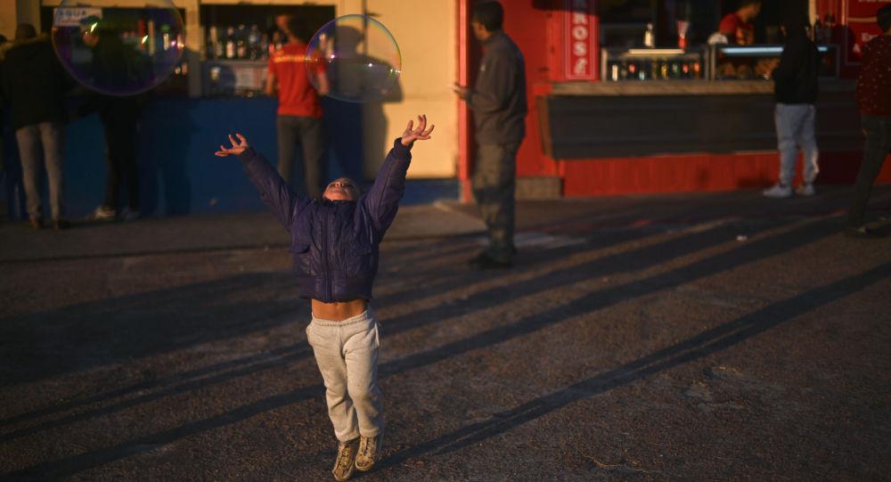 فتاة تحاول الإمساك بفقاعات الصابون في متنزه في مونتيفيديو ، أوروغواي 14 يوليو/ تموز 2019