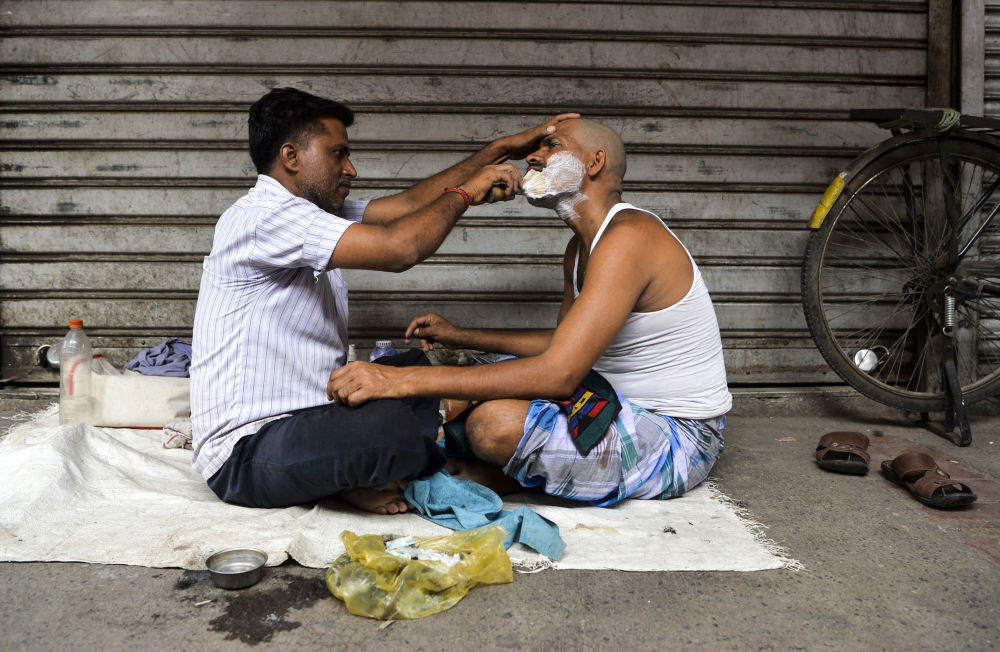 حلاق هندي في أحد شوارع نيودلهي القديمة، الهند 14 يوليو/ تموز 2019