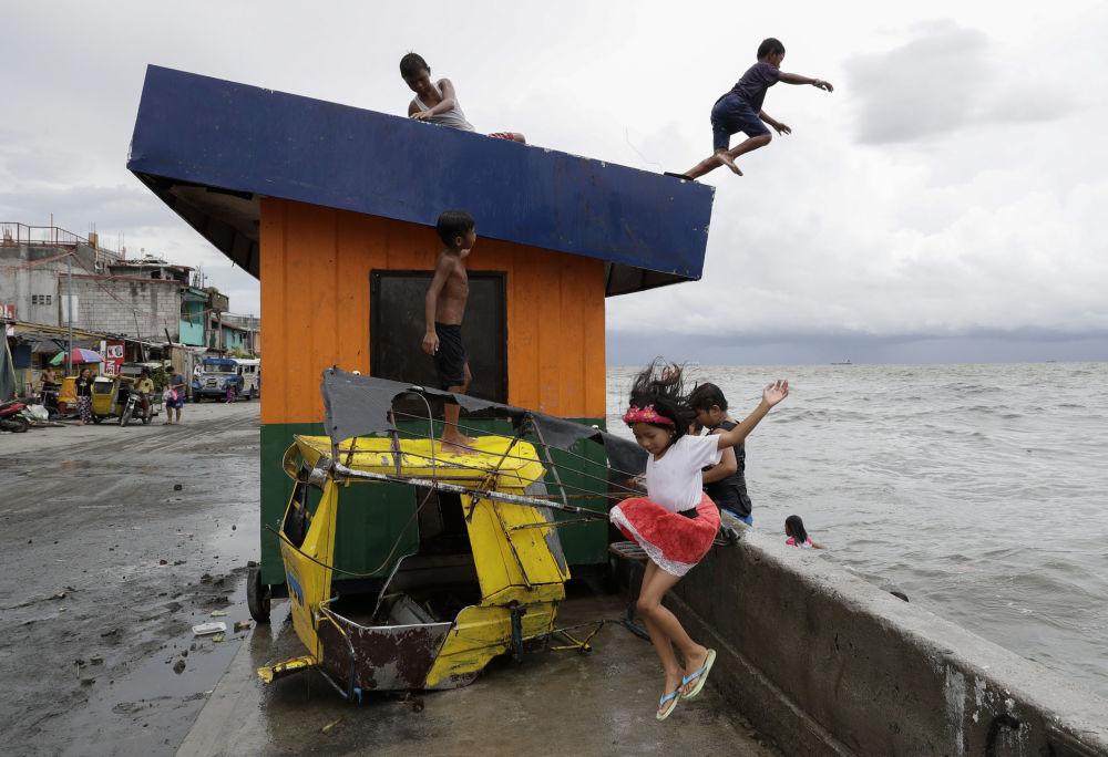 أطفال يقفزون إلى المياه في خليج مانيلا بالفلبين بعد هطول أمطار غزيرة