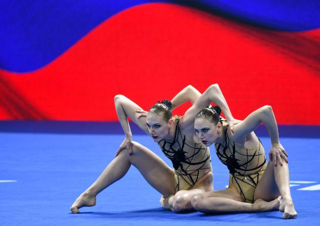 رياضيتان من المنتخب الروسي (سفيتلانا كوليسنيتشينكو وسفيتلانا روماشينا) تشاركان في البرنامج الفني لمسابقات فرق السباحة الإيقاعية في بطولة العالم المائية الـ18 في غوانغجو، كوريا الجنوبية 16 يوليو/ تموز 2019