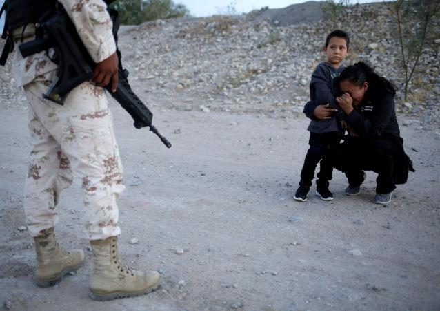 مهاجرة ليتي بيريز من غواتيمالا تحتضن ابنها أنتوني، وهي تتوسل إلى أحد عناصر الحرس الوطني المكسيكي لكي يدعهم يعبروا الحدود إلى الولايات المتحدة الأمريكية، المكسيك 22 يوليو/ تموز 2019