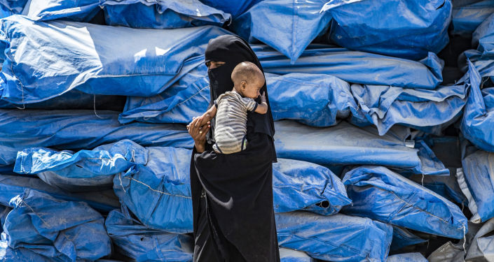 امرأة تحمل طفلاً في مخيم الهول للنازحين في الحسكة، شمال شرق سوريا 22 يوليو/ تموز 2019