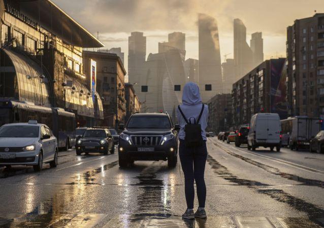 فتاة تتوقف على ممر للمشاة في حي كوتوزوفسكي بروسبيكت لتلتقط صورة لمجمع موسكو سيتي وسط موسكو.