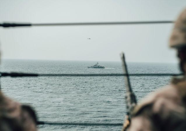 جندي من مشاة البحرية الأمريكية يراقب طائرة إيرانية هجومية من سفينة حربية أمريكية جون مورثا خلال مضيق هرمز في بحر العرب قبالة عُمان، 18 يوليو/ تموز 2019