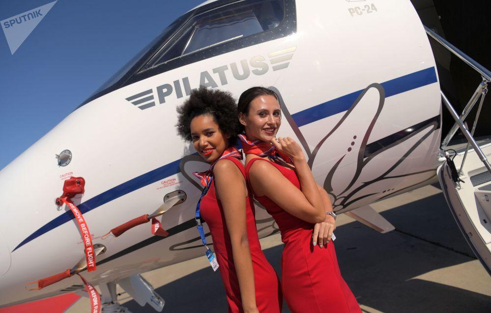فتيات المعرض على خلفية طائرة بيزنيس-جيت بيلاتوس بي إس-24 من سويسرا في المعرض الدولي ماكس 2019 في مطار جوكوفسكي