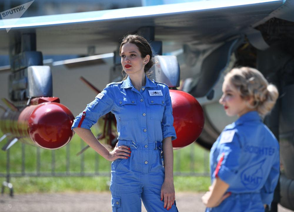 فتيات المعرض على خلفية طائرة ميغ-35 في المعرض الدولي ماكس 2019 في مطار جوكوفسكي