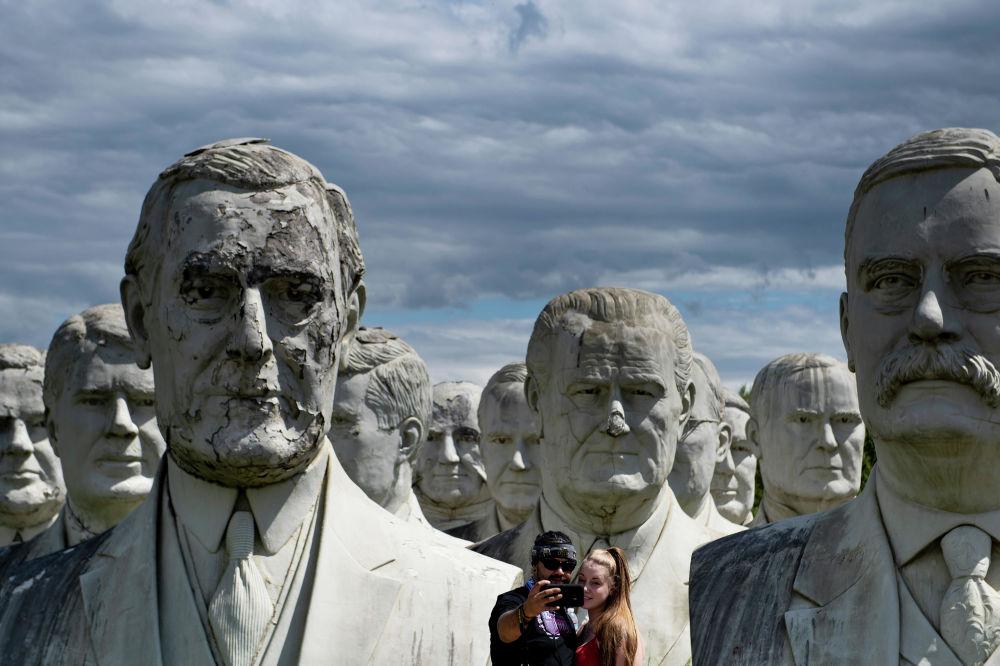 زوجان يطرحان صورة شخصية لهما تمثال نصفي عملاق تم إنقاذه من الرؤساء الأمريكيين السابقين في 25 أغسطس 2019، ويليامسبورغ بولاية فرجينيا. أنقذ هوارد هانكينز التماثيل العملاقة لرؤساء الولايات المتحدة السابقين من حديقة الرؤساء المغلقة في كولونيال ويليامسبورغ حينما كلّف بتدميرها