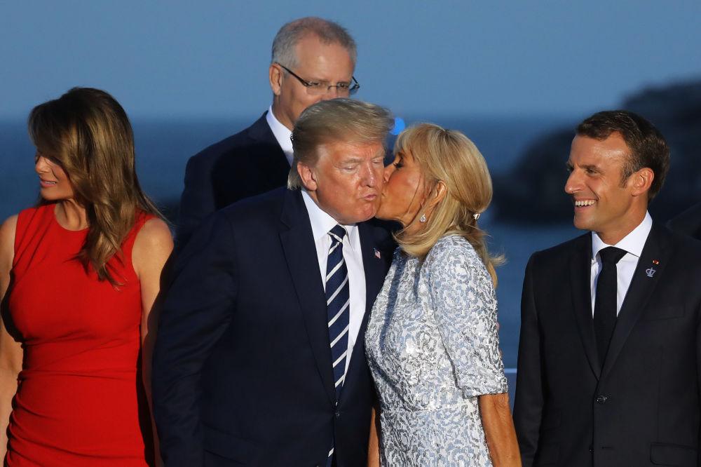 السيدة الفرنسية الأولى بريجيت ماكرون تقبّل الرئيس الأمريكي دونالد ترامب قبل التقاط صورة جماعية لزعماء مجموعة السبع وزوجاتهم في بياريتز، فرنسا 25 أغسطس/ آب 2019