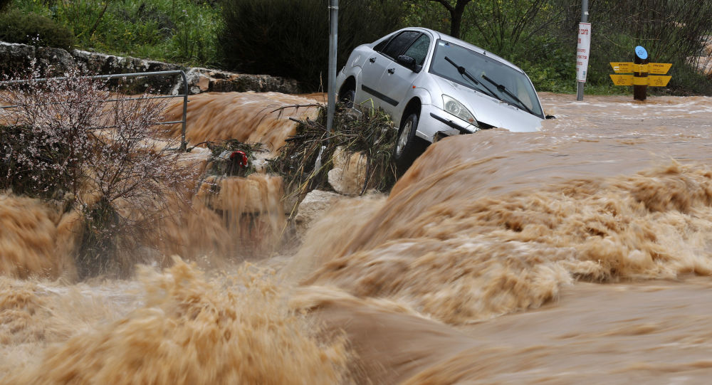 Flash floods caused by torrential rain go down a street on the outskirts of Jerusalem on February 28, 2019. (Photo by Ahmad GHARABLI / AFP)