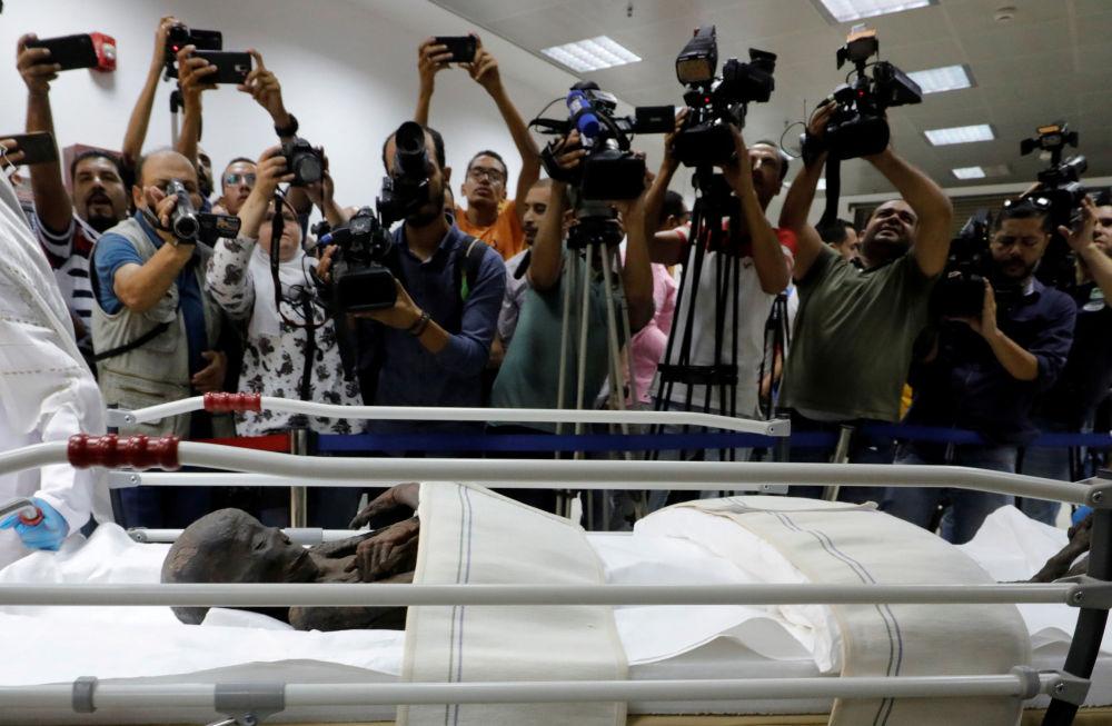 صحفيون يلتقطون صورا لمومياء سنجام، مسؤول العمال (رئيس العمال) خلال عصر الفرعون سيتي الأول ورمسيس الثاني للأسرة 19 (القرن 13-12 ق.م.)، في المتحف القومي للحضارة المصرية، 21 سبتمبر/ أيلول 2019