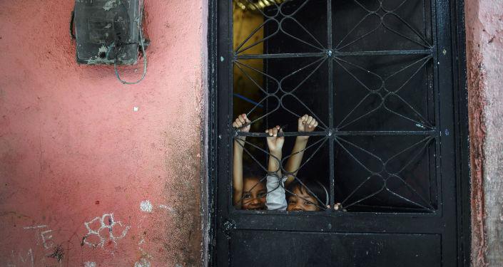 أطفال يلعبون خلف الباب، في بيتاري الفقيرة في كاراكاس، فنزويلا، 29 سبتمبر 2019