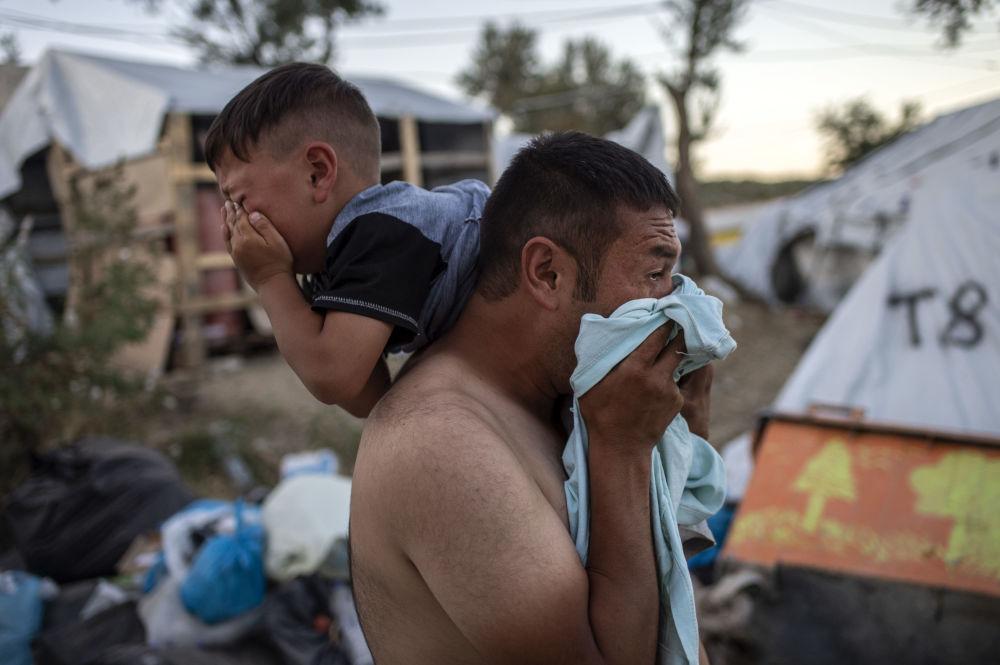 رجل مع طفل أثناء اشتباكات بالقرب من مخيم موريا للاجئين في جزيرة ليسبوس اليونانية، 29 سبتمبر 2019