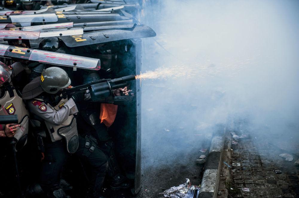 ضابط شرطة يستخدم الغاز المسيل للدموع خلال اشتباك مع الطلاب المحتجين ضد قانون جديد ضد محاربة الفساد في باندونغ، إندونيسيا 30 سبتمبر 2019