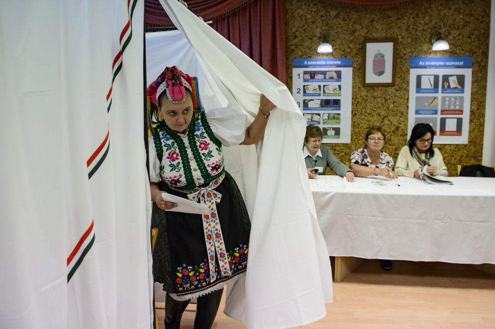 امرأة ترتدي الزي التقليدي الوطني، تغادر مركز الاقتراع حيث تقام انتخابات محلية في قرية ريموك في المجر، 13 أكتوبر 2019