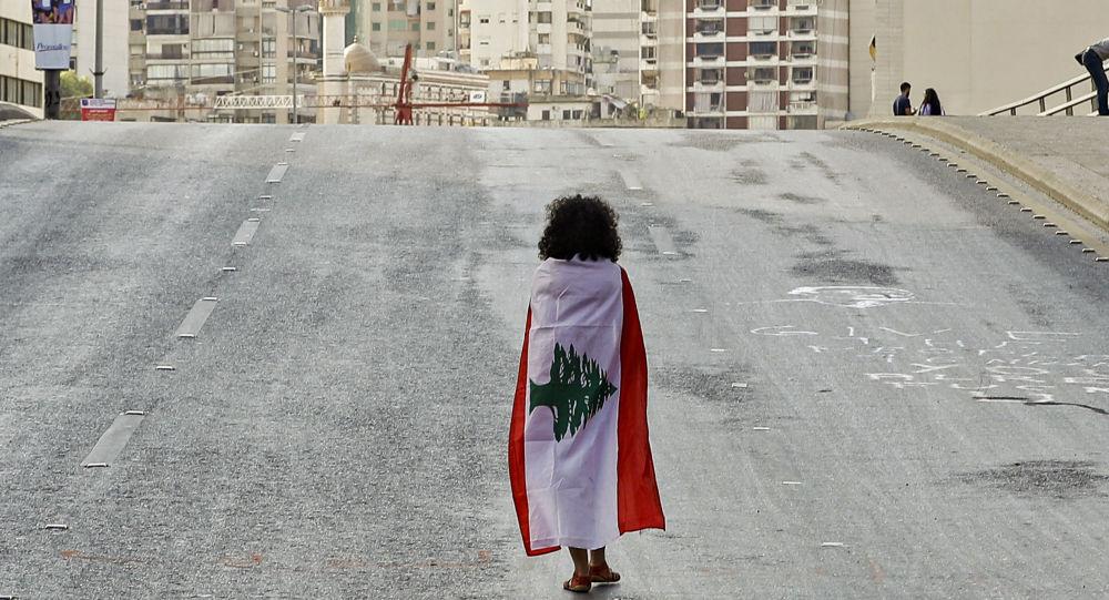 فتاة لبنانية تلتحف بعلم بلدها بالقرب من ساحة الشهداء بعد الاعتداء على الاعتصام