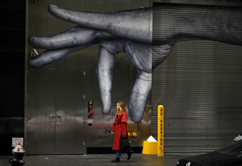 امرأة تسير على خلفية ملصق إعلاني في نيويورك، 27 أكتوبر 2019