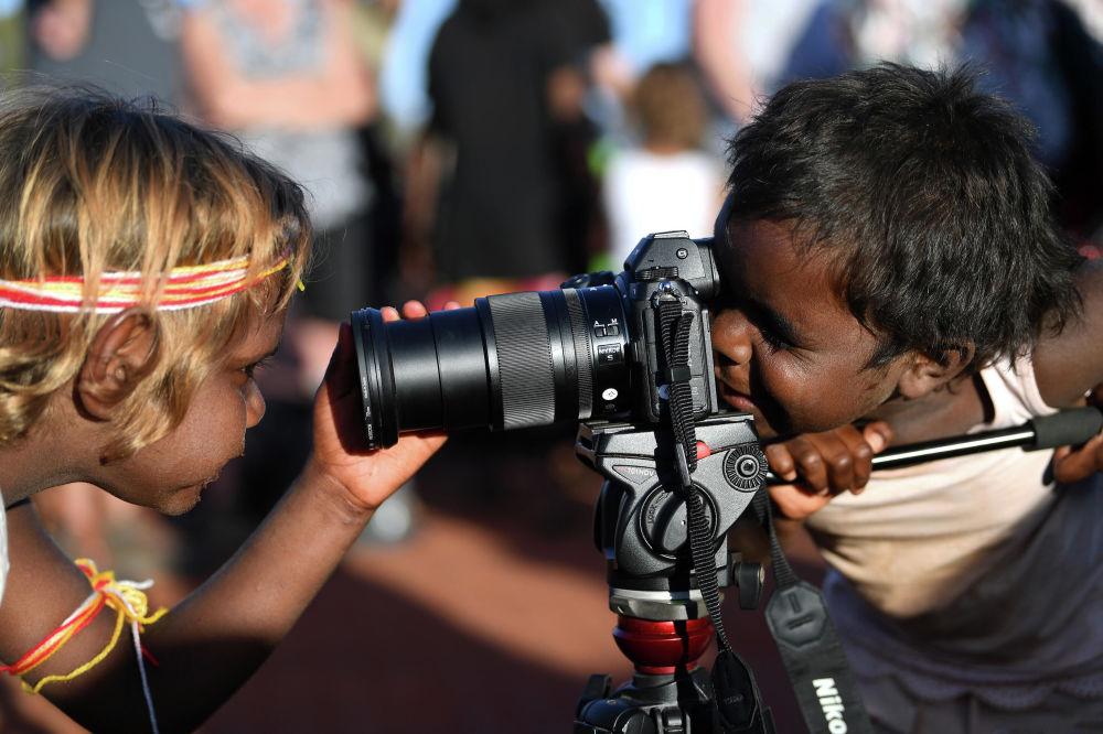 أطفال يلعبون بكاميرا التصوير في حديقة أولورو كاتا نخوتا الوطنية في أستراليا