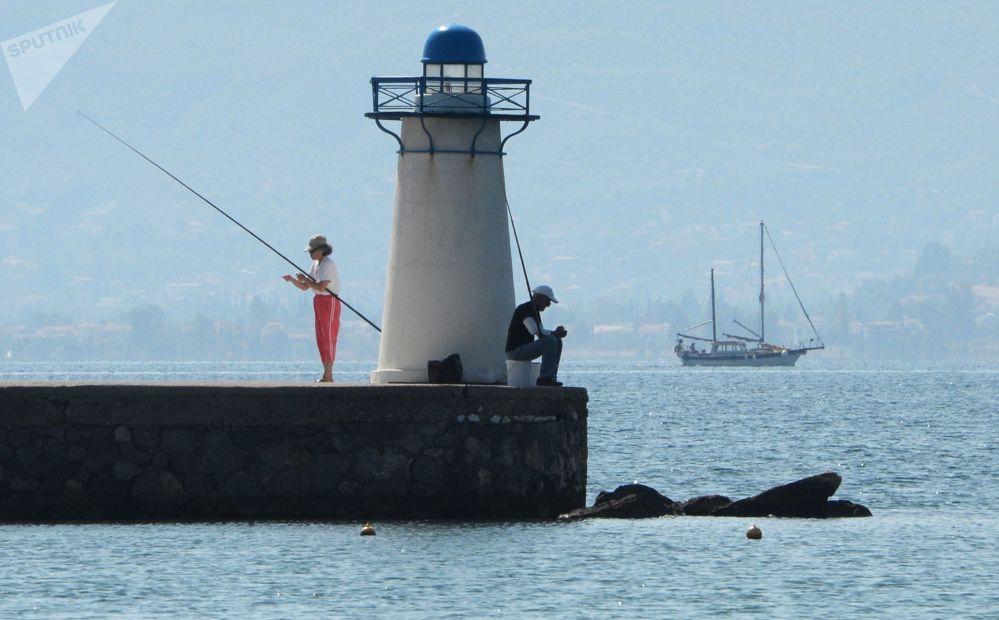 مصطافون يصطادون بالقرب من المنارة في خليج نوتيوس-إفويكوس في بحر إيجه