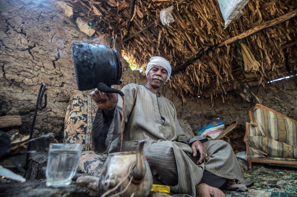 رمضان كامل، مزارع مصري يبلغ من العمر 71 عامًا، يعد الشاي في كوخ بالقرب من أرضه الزراعية في قرية بهرمس في ريف محافظة الجيزة، شمال غرب القاهرة، 1 ديسمبر 2019.