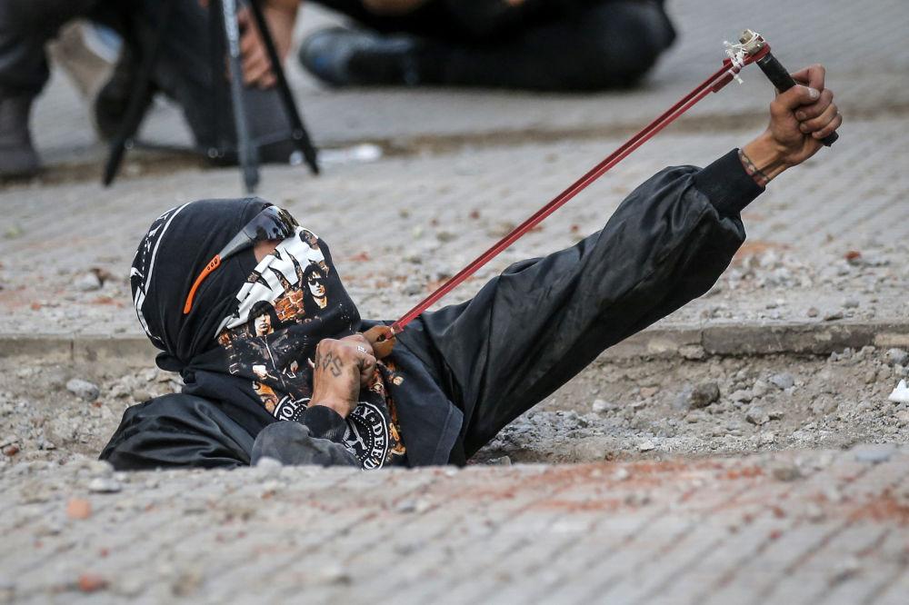 ناشطة تحمل مقلاعا خلال اللاحتجاجات على العنف القائم ضد المرأة والمجتمع الذكوري في سانتياغو، تشيلي 29نوفمبر 2019. وتستمر الاحتجاجات ضد عدم المساواة الاجتماعية والاقتصادية، وضد النخبة السياسية المحصورة في عدد من الأثرياء في البلاد، منذ 18 أكتوبر الماضي.