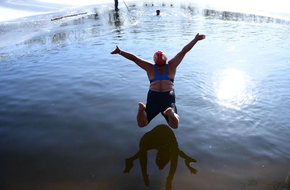 امرأة تقفز إلى مياه بحيرة متجمدة في حديقة شينيانغ في مدينة لياونينغ شمال الصين، 2 ديسمبر 2019