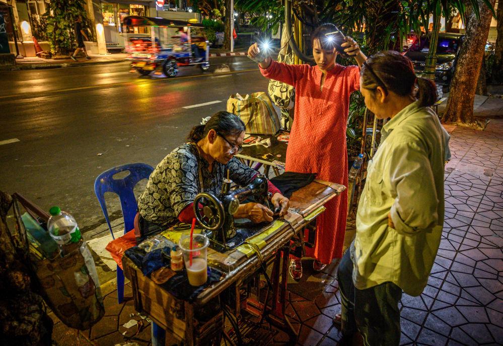 امرأة تستخدم إنارة الهواتف المحمولة لتساعدها أثناء الخياطة في أحد شوارع بانكوك، تايلاند 3 ديسمبر 2019