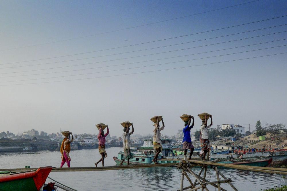 رجال يفرغون مواد البناء من سفينة شحن في غابتولي على مشارف دكا، 3 ديسمبر 2019