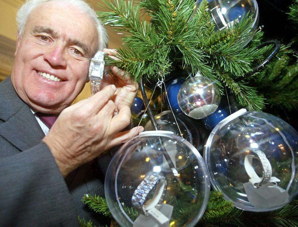 إيف بياجيه، رئيس شركة سويز ووتش وكجكوعة المجوهرات بياجيه السويسرية، يقف بجوار شجرة عيد الميلاد مزينة بجواهر مرصعة بالأحجار الكريمة والساعات الثمينة تقدر بسعر 11 مليون دولار في طوكيو، اليابان 2002