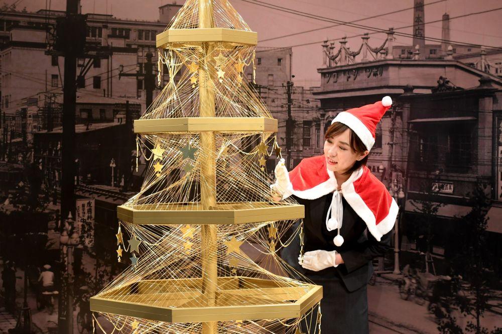 موظفة في بيت المجوهرات الياباني جينزا تاناكا (Ginza Tanaka) تعرض شجرة عيد الميلاد الذهبية التي تقدر بثمن 1.8 مليون دولار في طوكيو، 2016