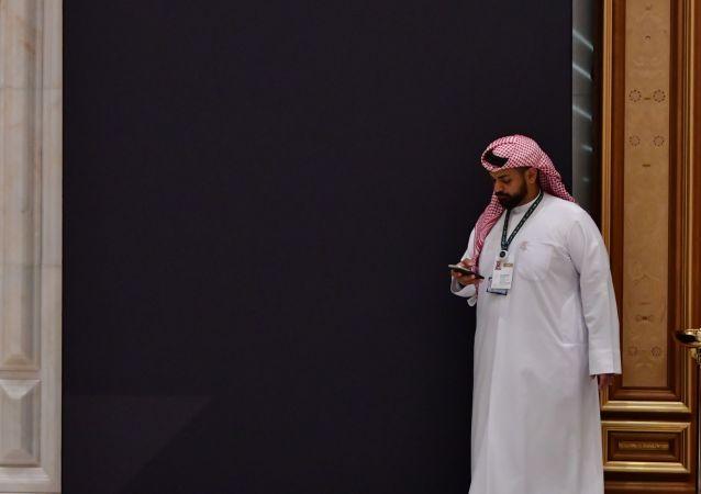 مواطن سعودي ينظر إلى هاتفه الذكي في العاصمة السعودية الرياض