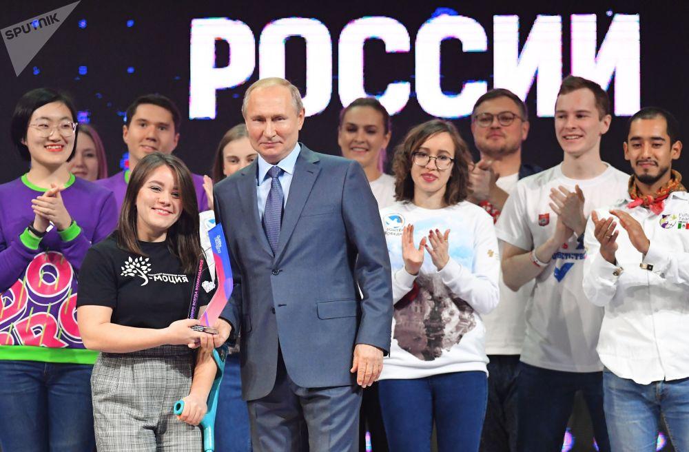 الرئيس الروسي فلاديمير بوتين يقدم الجائزة للفائزة، إنيسا كليوكينا، في مسابقة عموم روسيا التطوع لروسيا 2019 في ترشيح تطوع العام في ختام فعاليات منتدى متطوع روسيا، 5 ديسمبر 2019