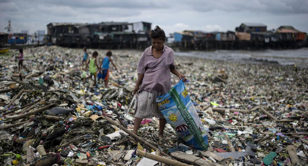 امرأة تجمع النفايات البلاستيكية على خليج مانيلا في الفلبين