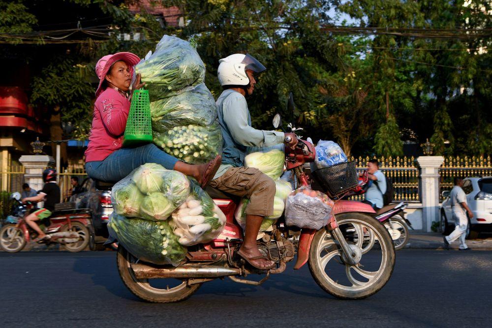 مواطنون محليون يحملون الخضروات في بنوم بنه، كمبوديا 22 يناير 2020