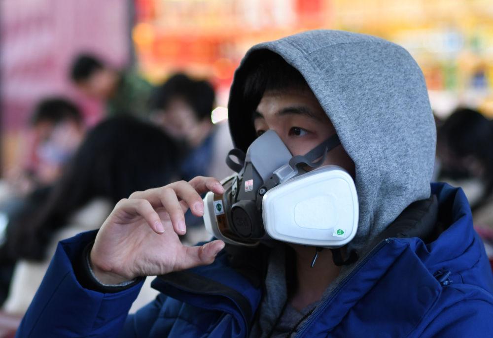 شاب يرتدي قناعا واقيا في محطة القطارات في مدينة بكين الصينية، 24 يناير 2020