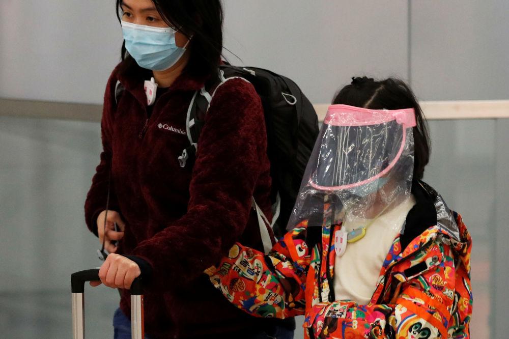 امرأة وطفلتها يرتديان أقنعة واقية لدى وصولهما إلى محطة القطارات في هونغ كونغ، 29 يناير 2020